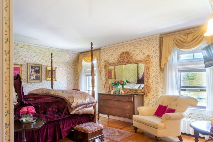This queen bedroom on the 3rd floor features an elegant high four poster bed, TV, bathroom and mini fridge.