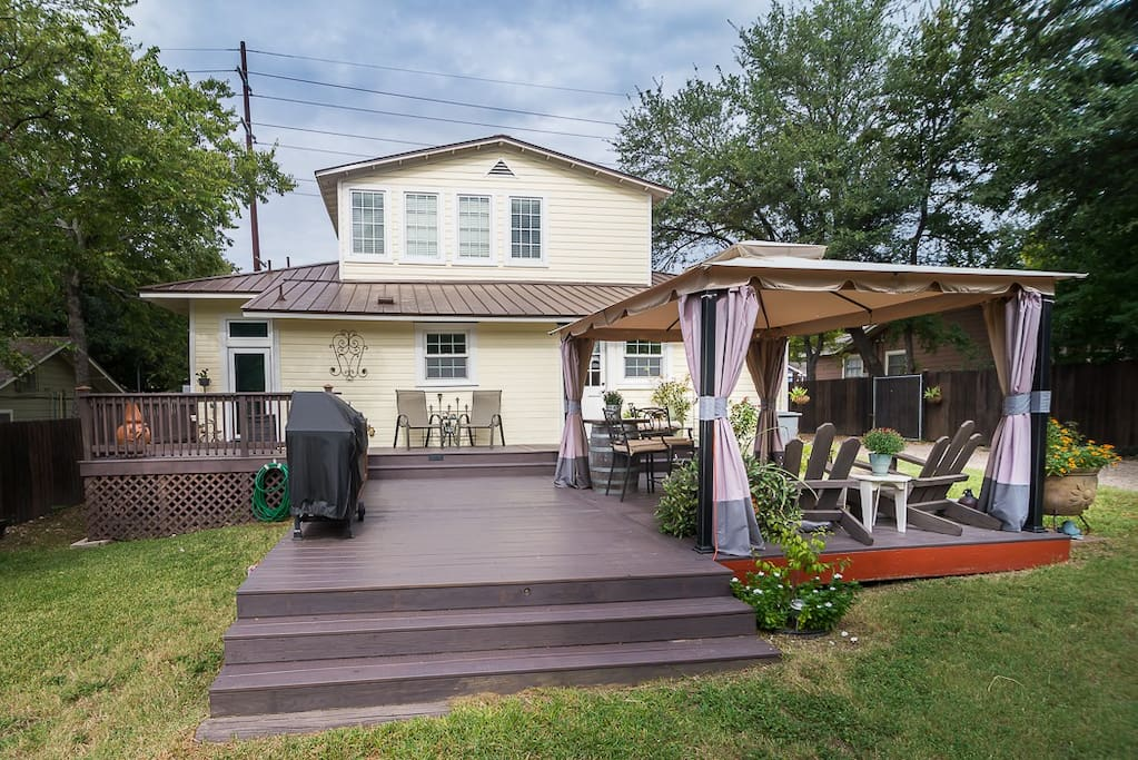 Large back yard with large deck, outdoor kitchen, canopy with screens, and fountain
