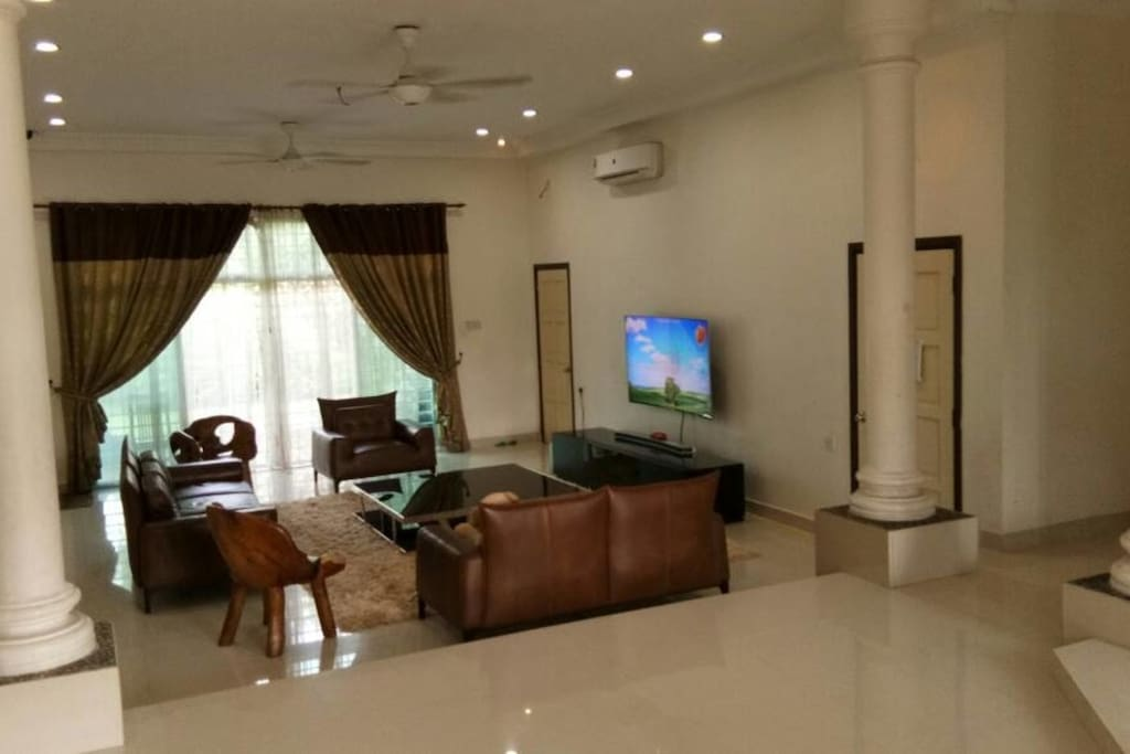 Living area with leather sofa and 65 inches WiFi Curved TV.