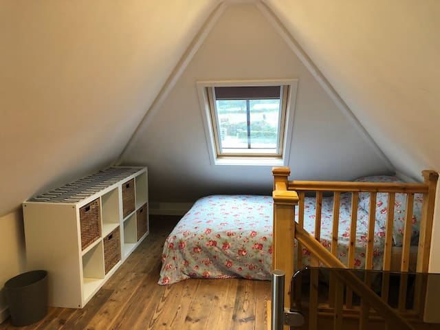 Light and airy bedroom with Small double bed. Lights are on dimmer switches. Ancient wooden floor boards.