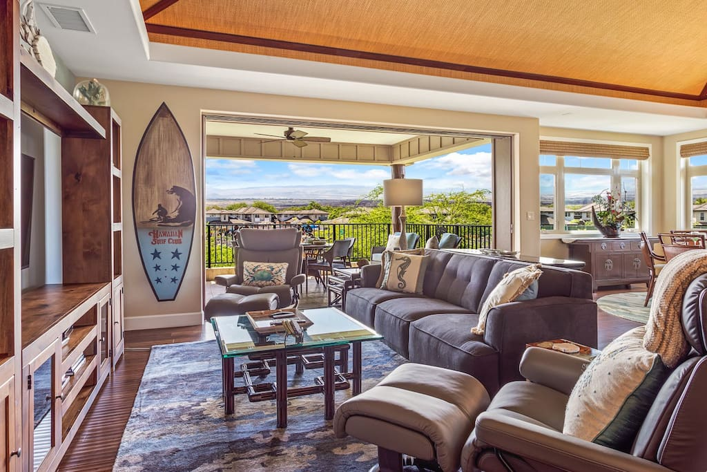 Living area with 55 inch smart flatscreen TV with view to upper lanai, vaulted grasscloth ceilings over entire open floor plan great room.