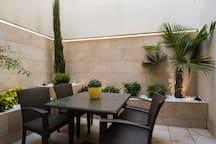 Terraza con palmera, cipres y plantas aromáticas. Dispone de riego automático y luz de led nocturna.