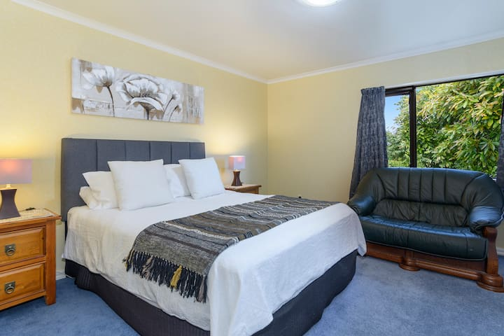 """Bedroom 4 Yellow Room double bedroom with afternoon sun. Queen bed and two seater couch. Double wardrobe. Heater. Insect screen. """"A very nice house to stay with friends. The garden is beautiful and we enjoyed our BBQ brunch outdoor.""""- Yun, Sept 2020"""