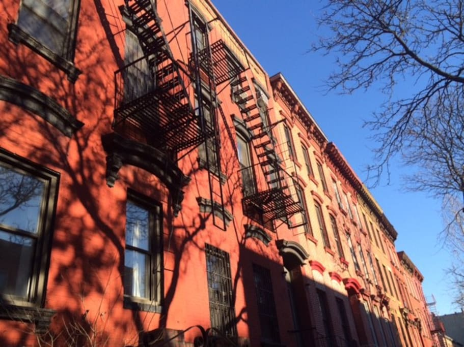 View of our red brick 4-family townhouse, featuring a classic New York City fire escape.