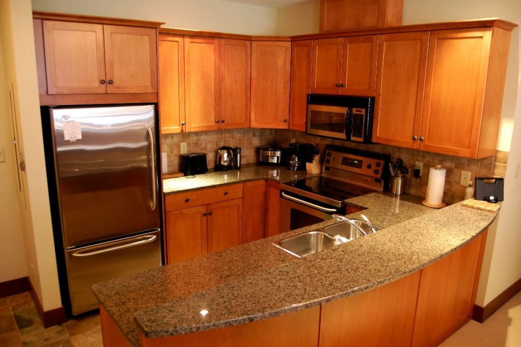 The fully-equipped kitchen features stainless steel appliances.