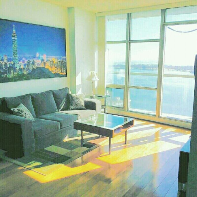 Living Room. Lots of sunlight and beautiful lake views all day with no buildings in front of you. (Can leave the blinds open ALL day)