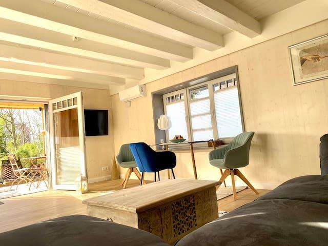 Wohn-/ Esszimmer mit Airconditioner und Blick auf die Terrasse.