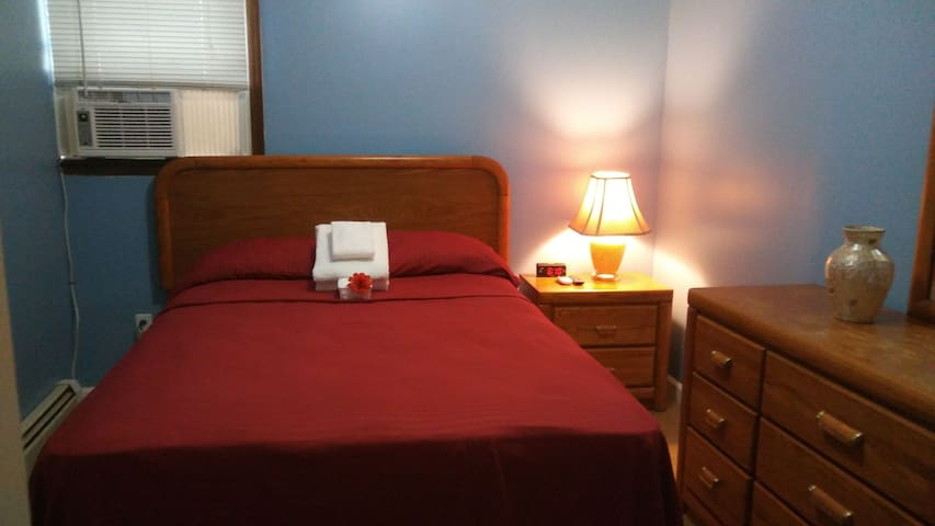 Nicely laid out Bedroom with Full Sized Bed, Air Conditioner, Night Stand, Clock Radio, Bed Side Lamp
