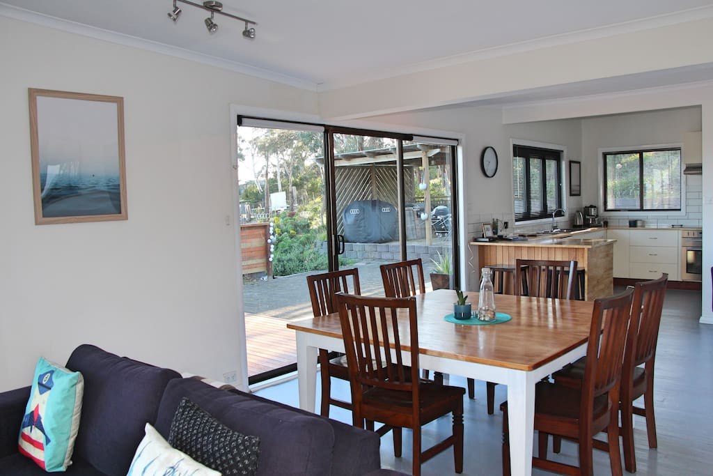 Large kitchen, six seat dining table and open plan living area with plenty of space that opens onto private decks.