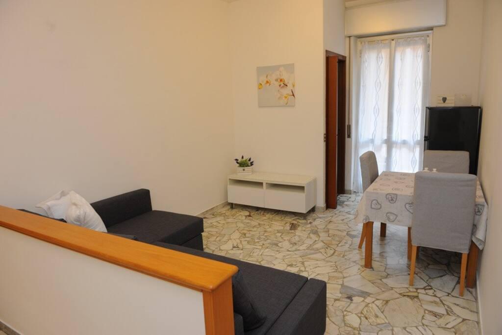 Soggiorno con divano, tavola e frigorifero (con balconcino interno)