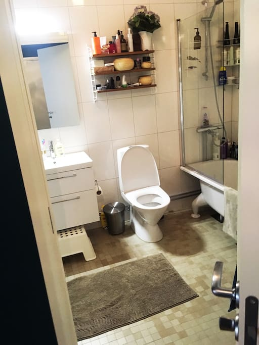 Badrum med badkar, toalett, tvättmaskin och torktumlare