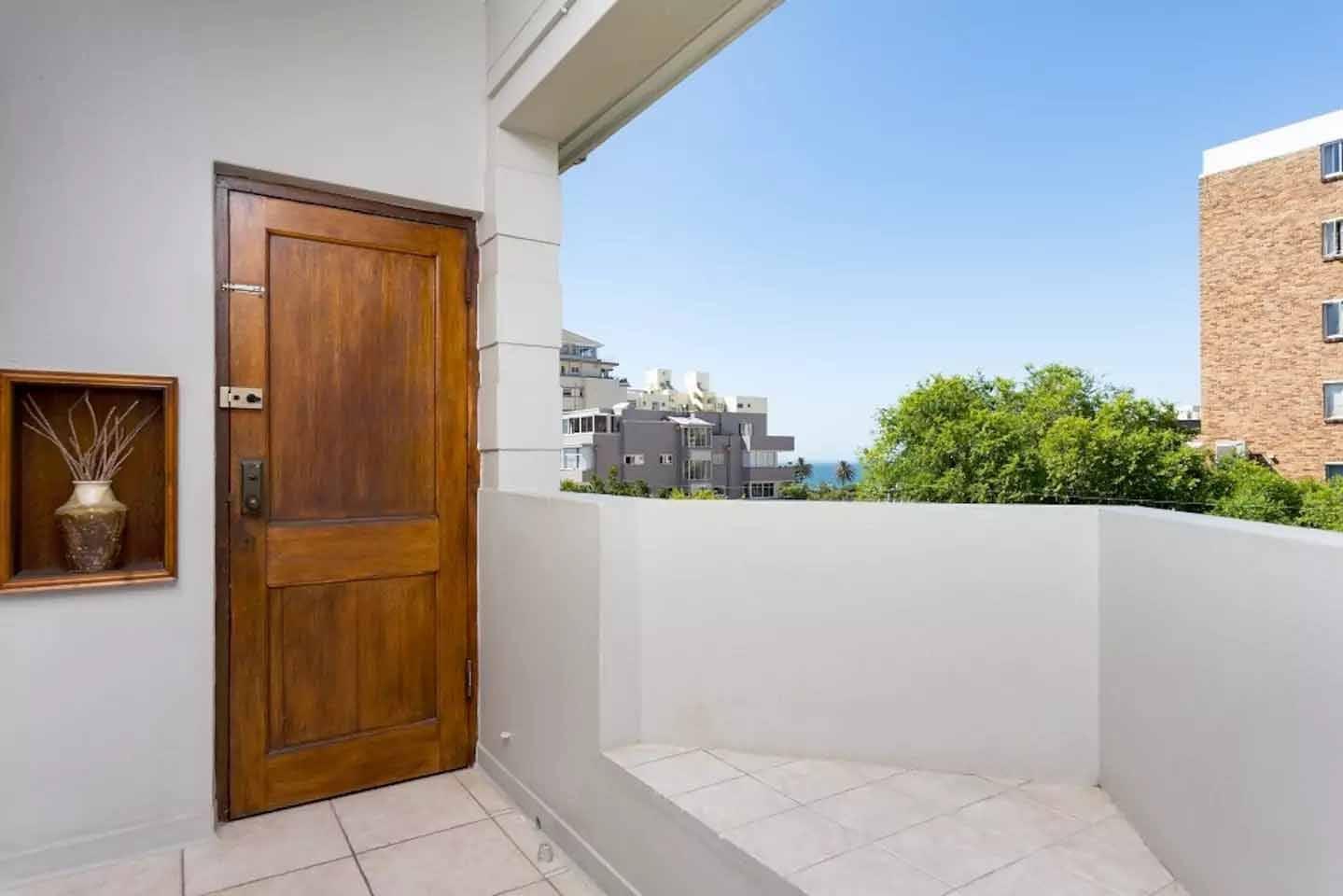 Entrance door, bright balcony and a peak at a sea