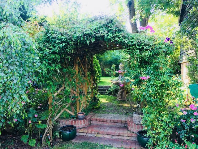 Beautiful rose arch in the garden, with fountain