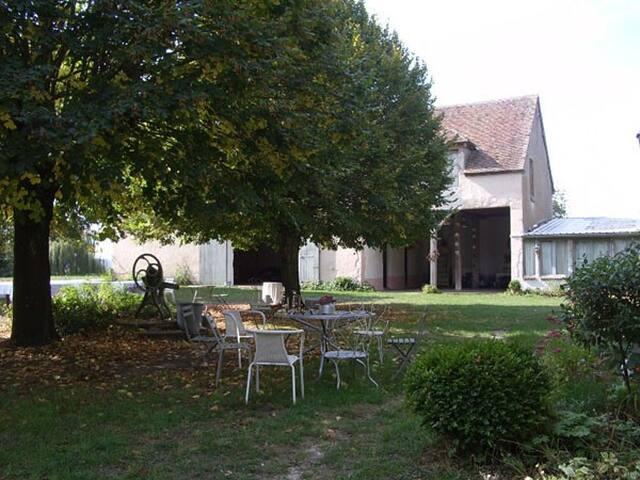 Le salon de jardin devant la grange d'été et la remise