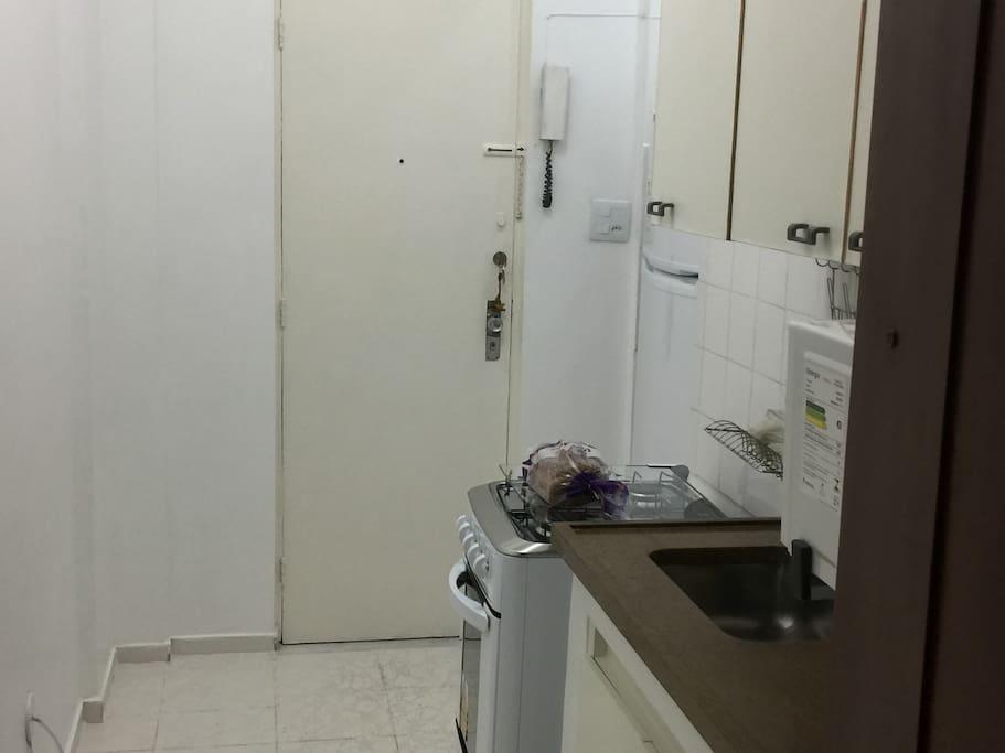 Cozinha (geladeira, fogão, forno microondas, cafeteira, sanduicheira-grill, liquidificador, pratos, copos talheres, armários e pia grande).