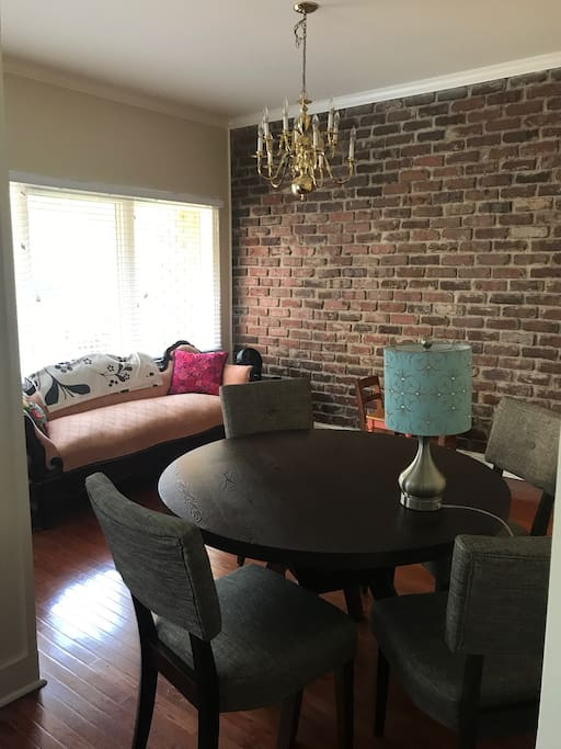 Dining room with table for 4, kids table for 2, and vintage couch.