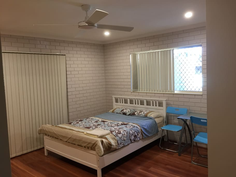Large bedroom with queen side bed and study desk.