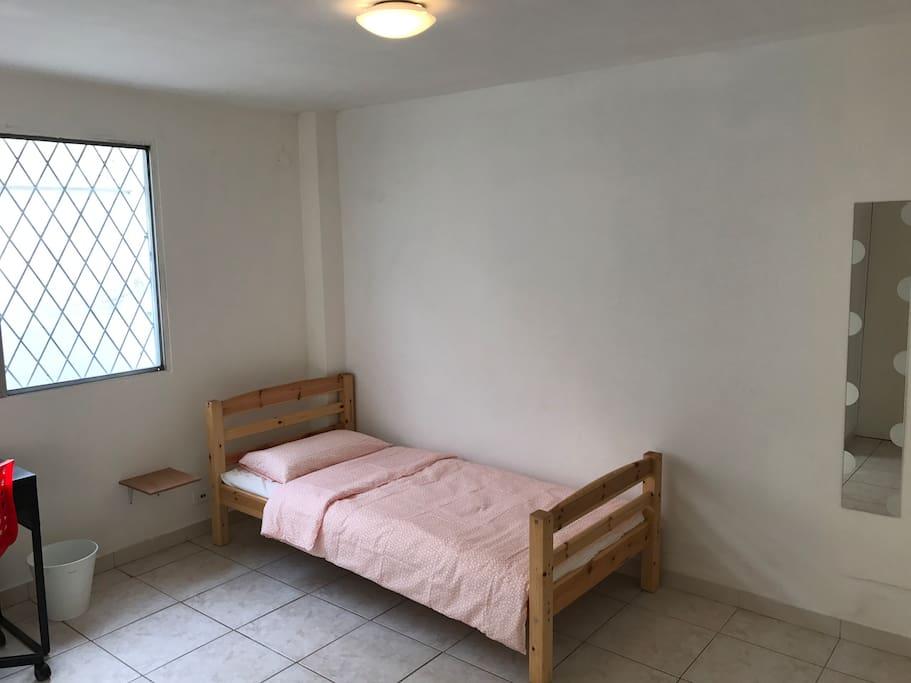 Habitación individual con escritorio y espejo