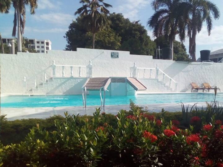 Habitación con baño privado y piscina.