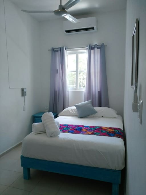 Bedroom a Doble bed, bath towels a small lamp on the bureau, a mirror on the wall, A.C  remote and roof fan.