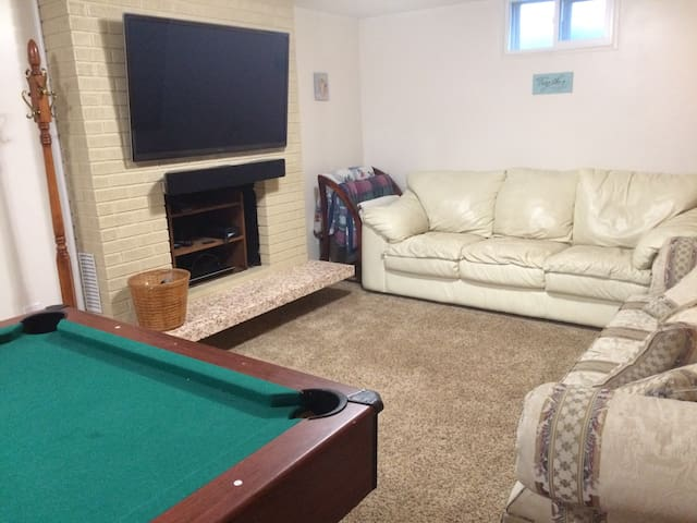 Living room showing couches, TV with soundbar, and pool table.