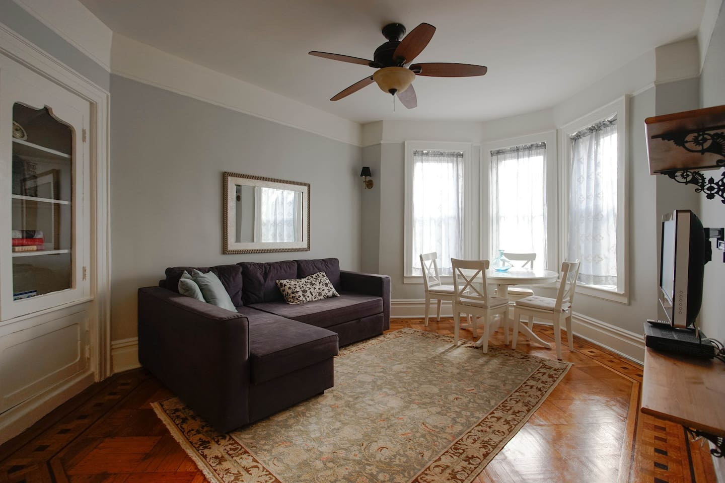 Spacious sunny living room features a queen-sized sofa bed and original wood floors with radiant heat.