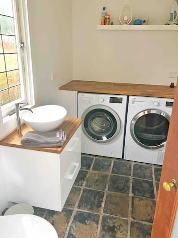 Laundry with washer and sensor heat pump dryer as well as second toilet.