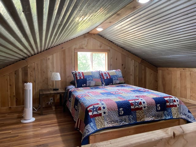 Queen bed in loft area with comfortable Zinus memory foam mattress.