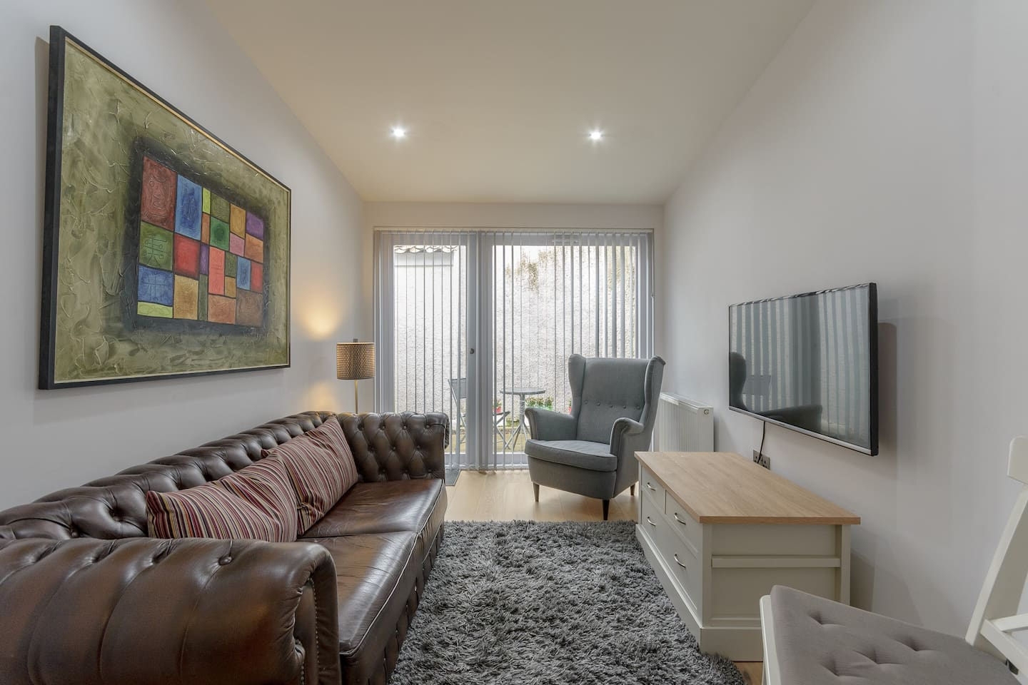 Modern, brightly-lit living room with large flatscreen TV, comfy chesterfield sofa, and hi-speed wifi.