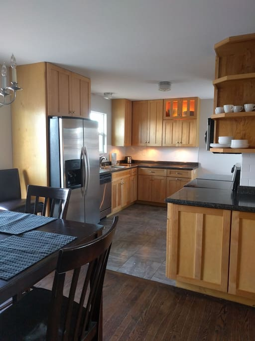 Renovated fully equipped kitchen,  microwave, side by side refrigerator, dishwasher glass top range.