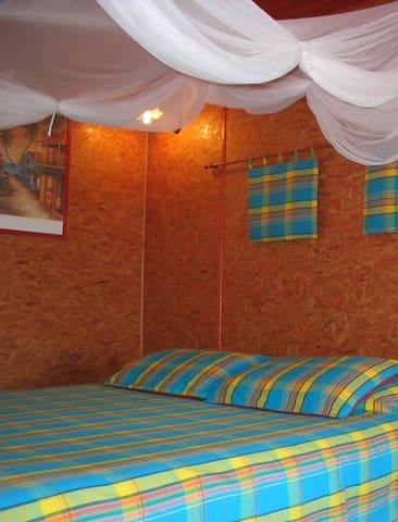 Chambre spacieuse avec moustiquaire et brasseur d'air