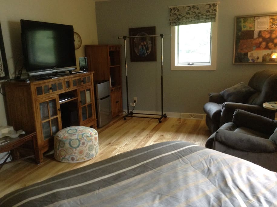 The guest bedroom has a clothing rack, mini fridge and TV