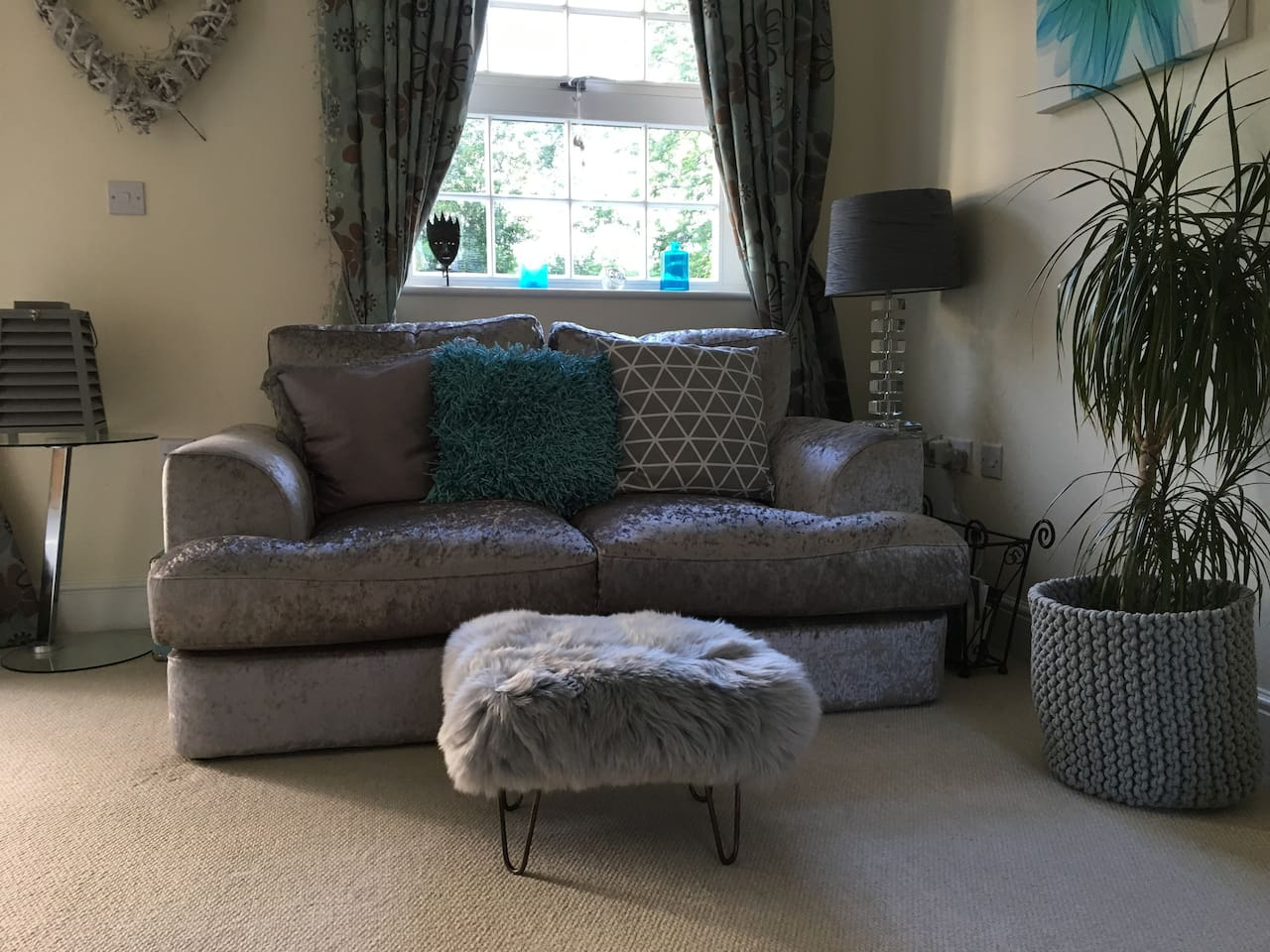 Living Room with Two Quirky Comfortable Sofas and Unique Contemporary Silver Sheepskin Baa Footstools to Relax and Put your Feet up