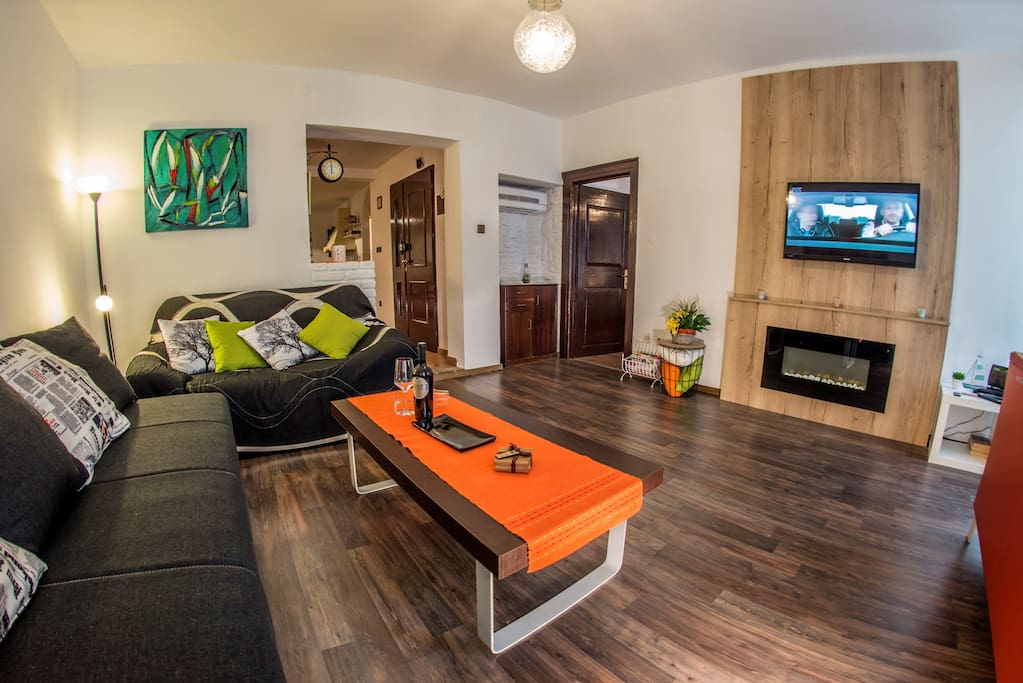 Living room with flat screen TV, air condition, electric fireplace and extendable sofa