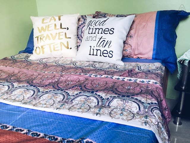 Comfortable semi-double bed with colorful linens, bedsheet and pillows