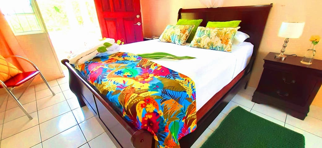 bedroom 4 with pool and garden view, double bed,  wardrobe, chair, reading lamp, air conditioning,mosquito net and rear access to pool