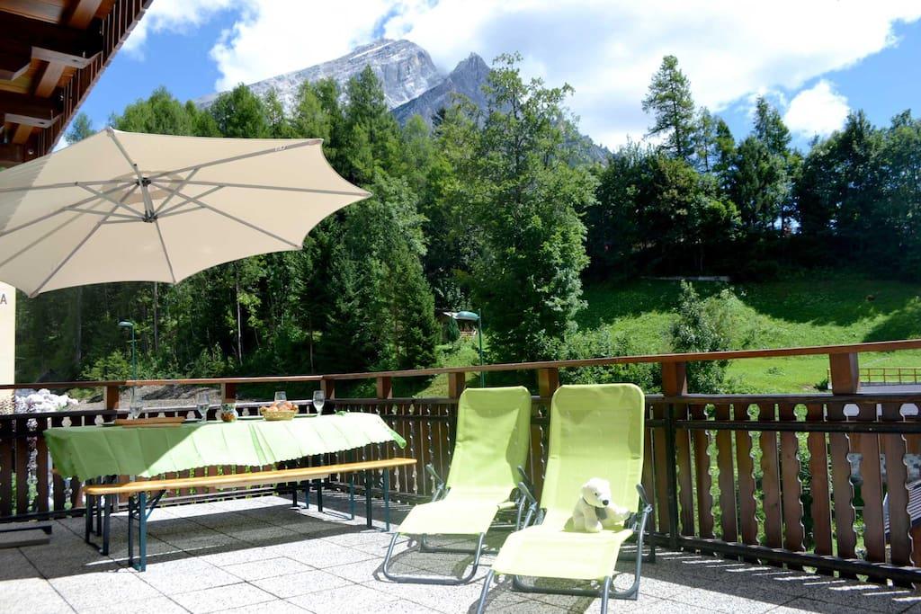 Terrazza con ombrellone, sedie a sdraio, tavolo e panche (se non bastasse il panorama)