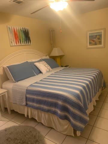 Master bedroom features a comfortable king size bed, flat screen tv, and a balcony.