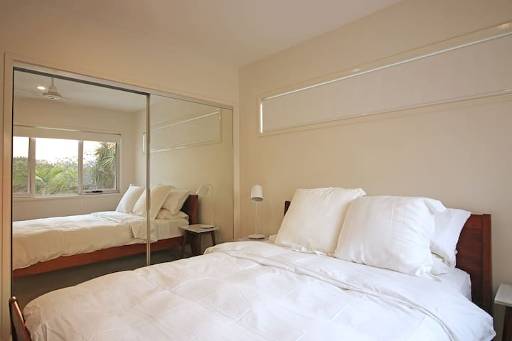 The upstairs queen size bedroom with built-in wardrobe.