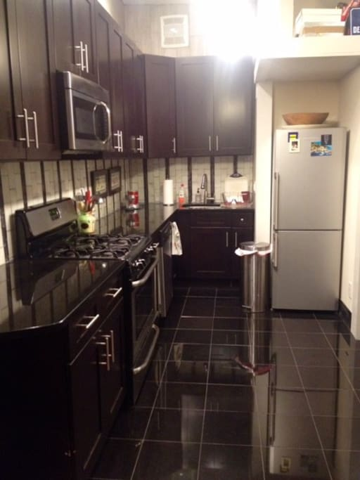 New kitchen with oven, microwave, dishwasher, refrigerator, dishes, glasses, utensils, and pots and pans.