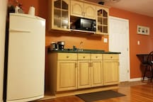 kitchenette with toaster, coffee machine, microwave and refrigerator.