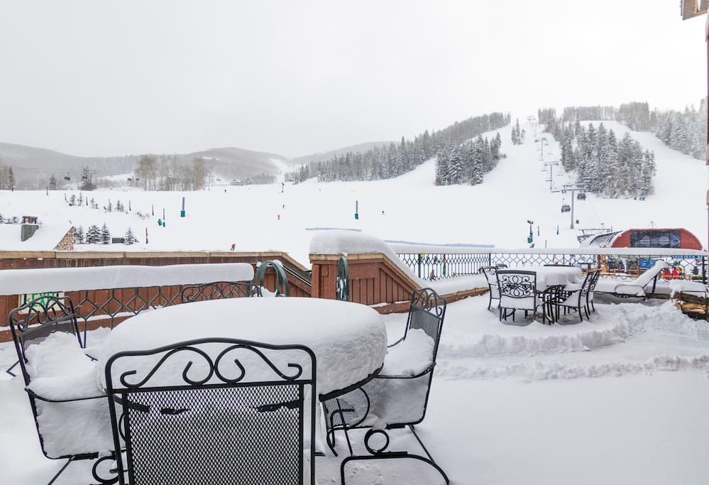 A wide flagged patio looks out to the chair lift