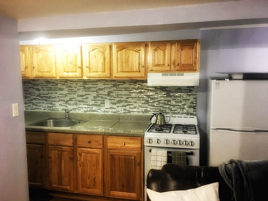 Complete kitchen setup including refrigerator/freezer, coffee pod machine, microwave oven, stove, pots, pans, and dishes.