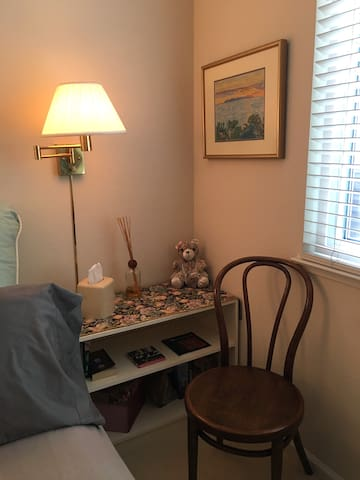 Side shelves and chair in your bedroom with kleenex, books, candles, and filtered water.