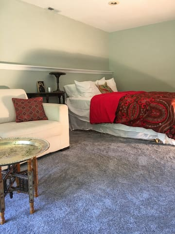 Queen bedroom with couch and French doors to garden.