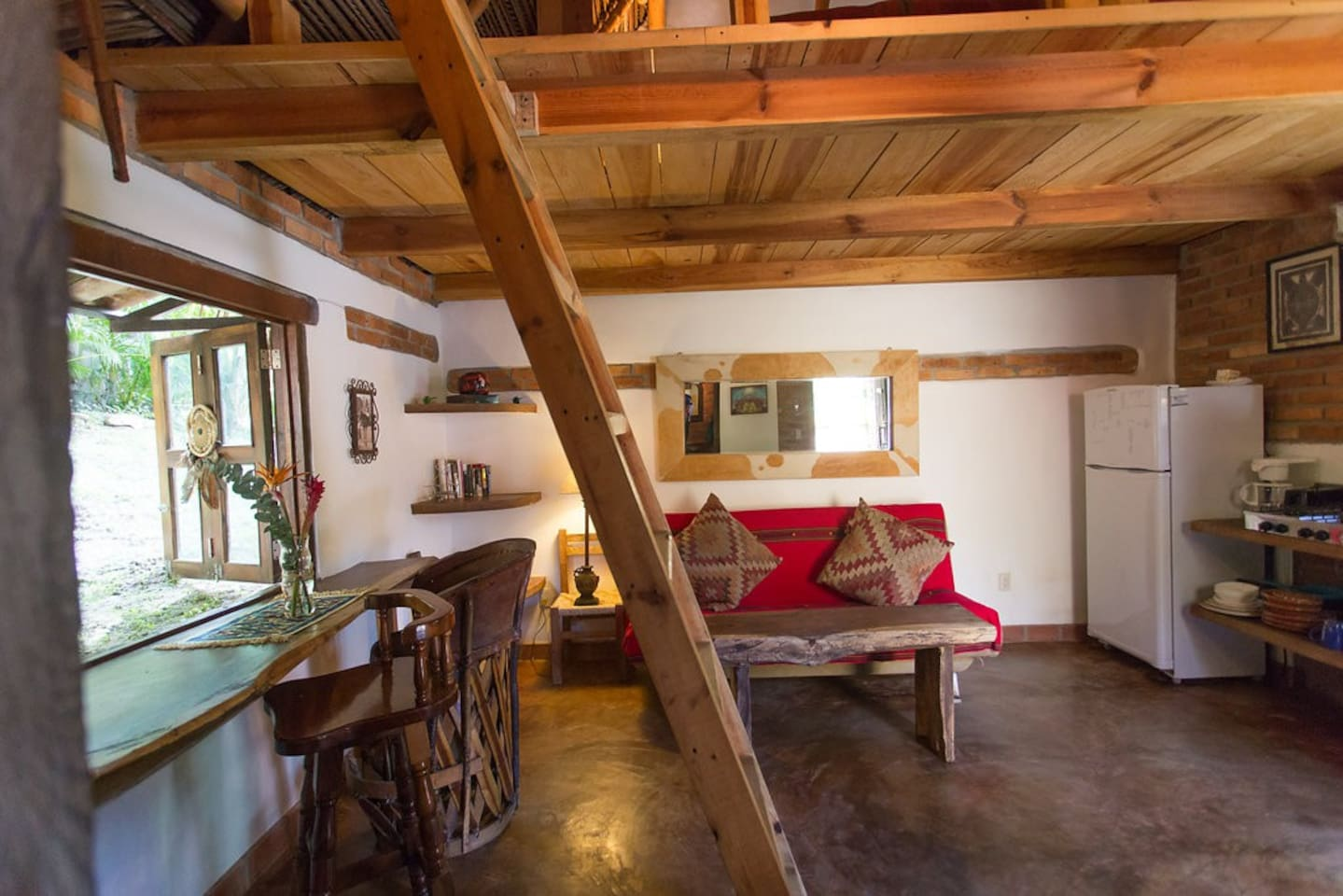 Inside the bungalow there is a futon couch, and a counter for eating. The king sized bed is upstairs in the loft.