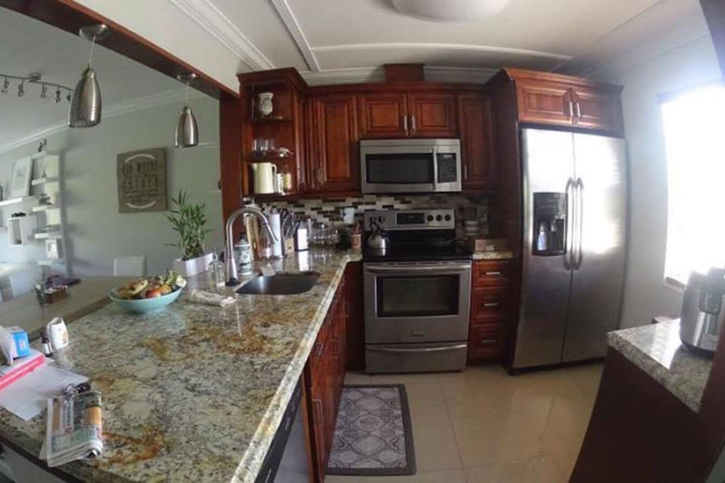 Open spaced kitchen. With fridge, oven, microwave, utensils, plates and dishwasher.