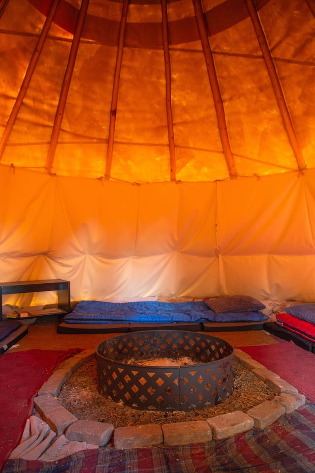 Inside Tipi, firepit and mattresses, table