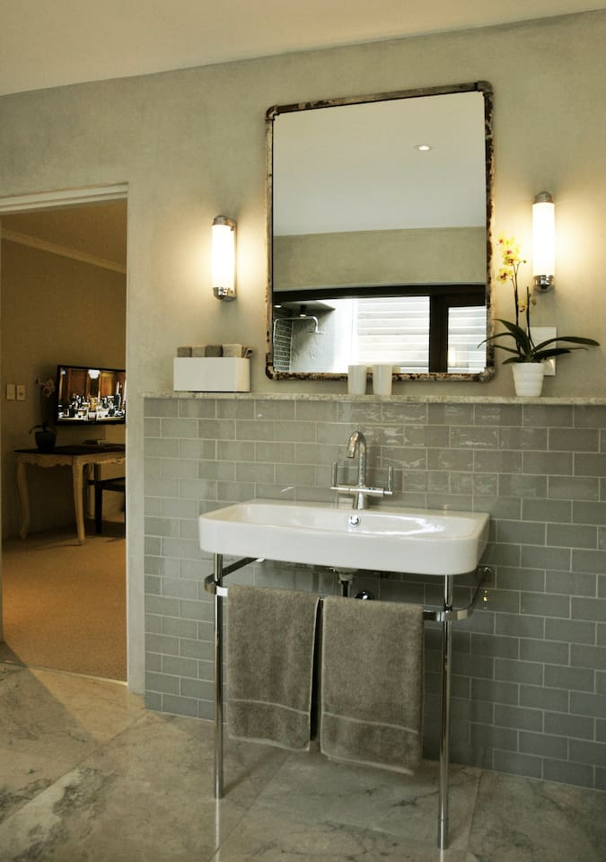 Freestanding basin and glass tiles offer a luxurious stay.