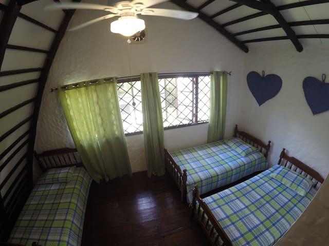 Cuarto secundario con 3 camas individuales y cama de piso.